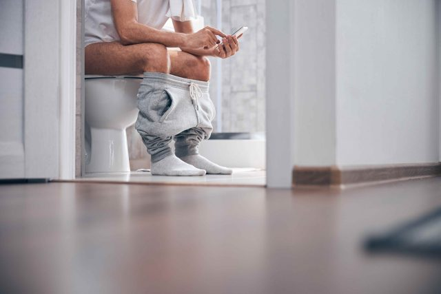 The picture shows a man sitting on the toilet