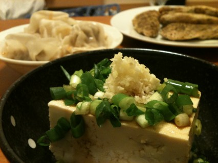 tofu garnished with minced ginger, garlic, and green onions.