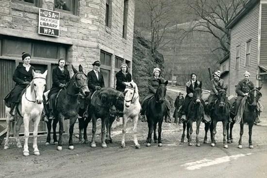 """Vemos uma foto preto e branco de oito mulheres montadas em cavalos abaixo de uma placa que diz """"USA PACK HORSE LIBRARY - WPA"""" nome dado a biblioteca itinerante a cavalo."""