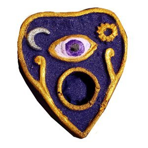 Ouija planchette bath bomb. It is shaped like an upside down tear drop. It is dark purple with a small sun on one side, and a small crescent moon on the other. In the center is an open eye, also painted purple. The rim is painted gold.