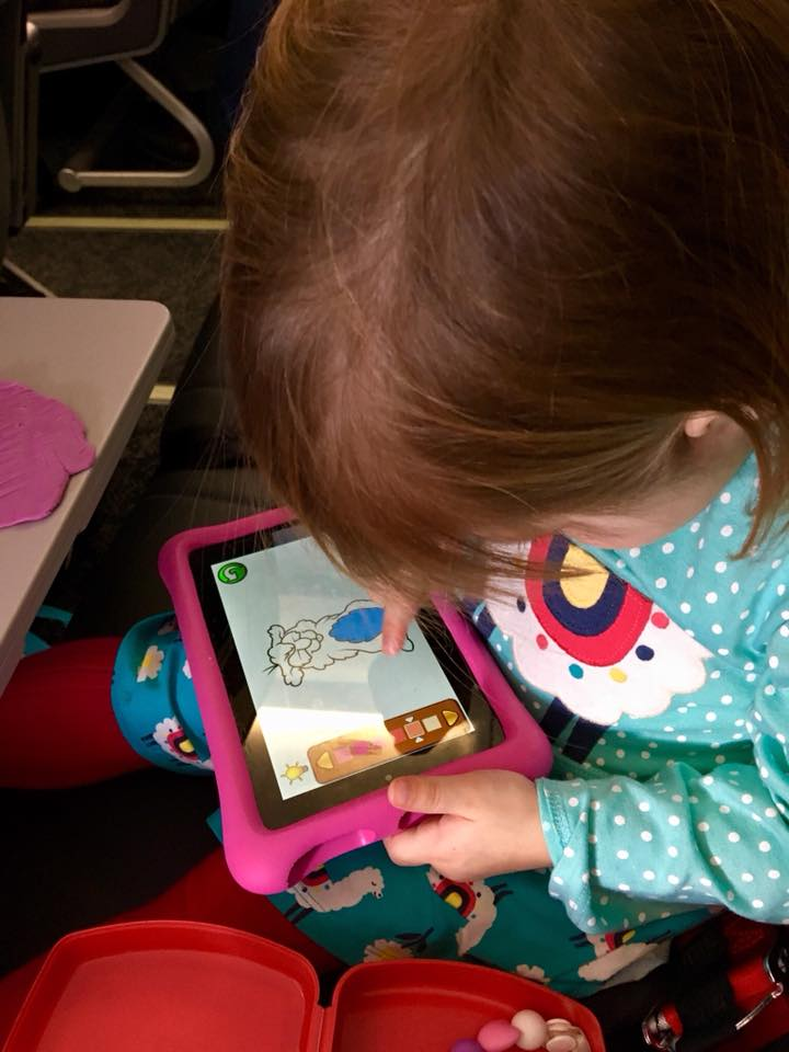child paling on her kindle in the airplane