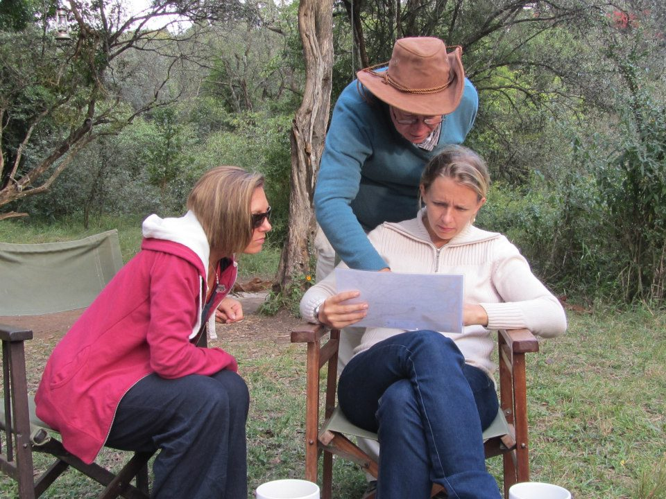 three people reading a map to set a route for a cycling safari