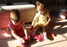twins getting ready fr nursery by putting their shoes on