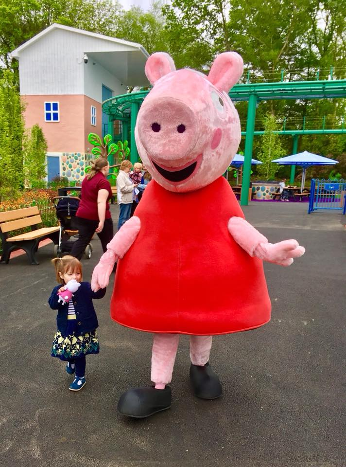 Twins at Peppa Pig World playing and smiling with the characters