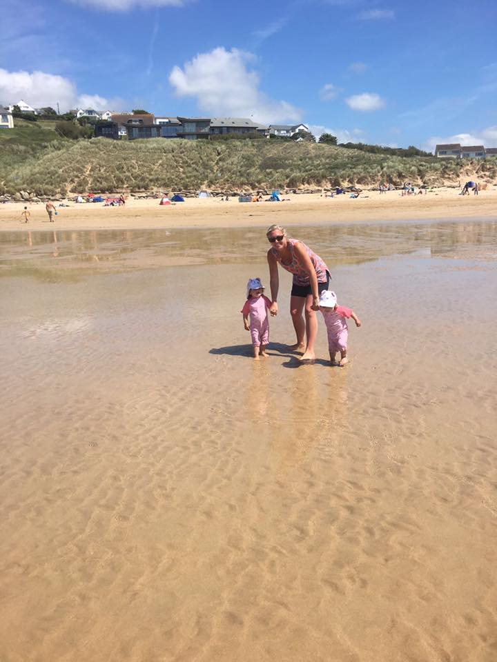 beach in Cornwall with twins playing in the water