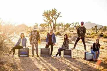 Sechs Bandmitglieder in der Wüste