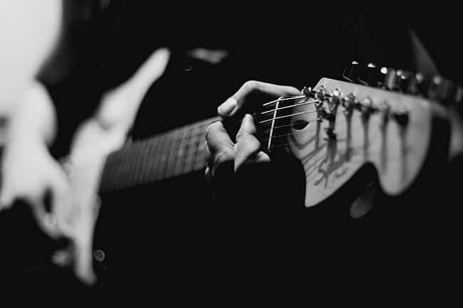 Schwarz-Weiß Bild: Mann hält eine Gitarre