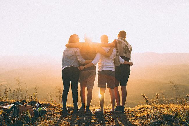 Vier Freunde halten sich im Arm