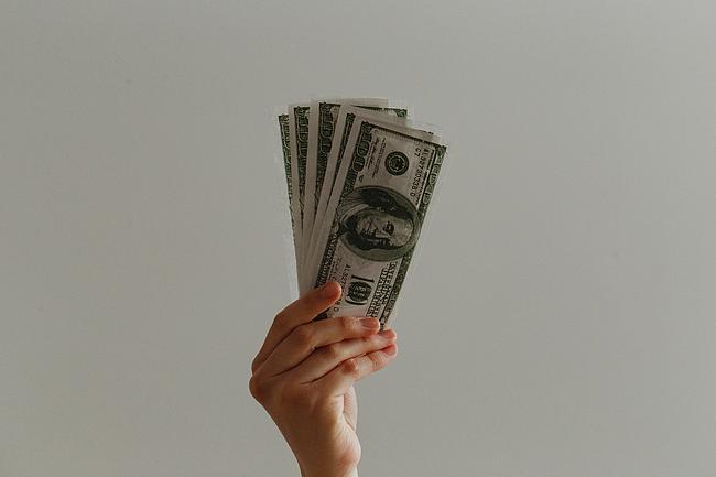 Geldscheine werden von einer Hand in die Höhe gehalten