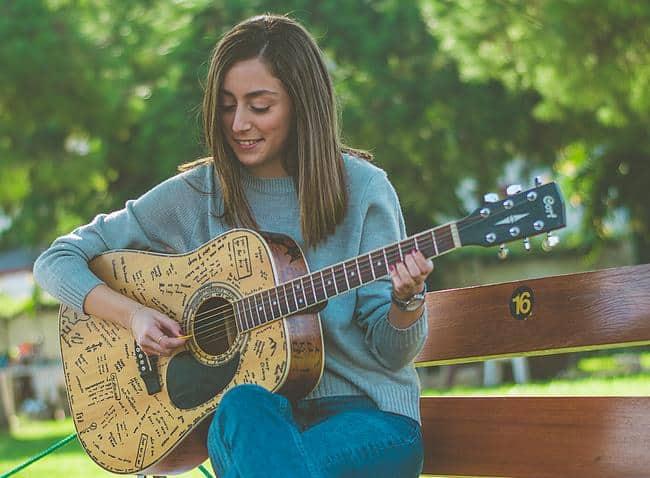 Frau sitzt mit Gitarre auf einer Bank
