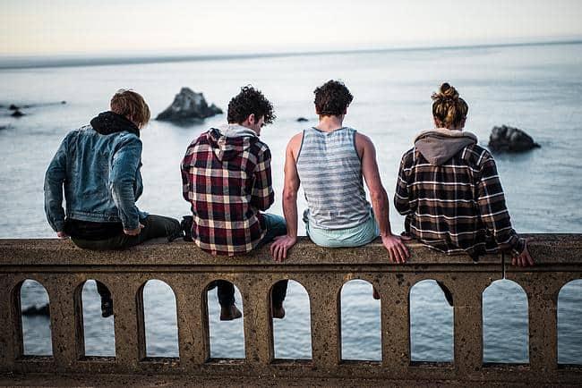 4 Jugendliche sitzen auf einer Brücke