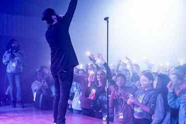 Junger Sänger steht auf einer Bühne vor Publikum