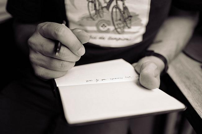 Mann hält Stift und Notizblock in der Hand