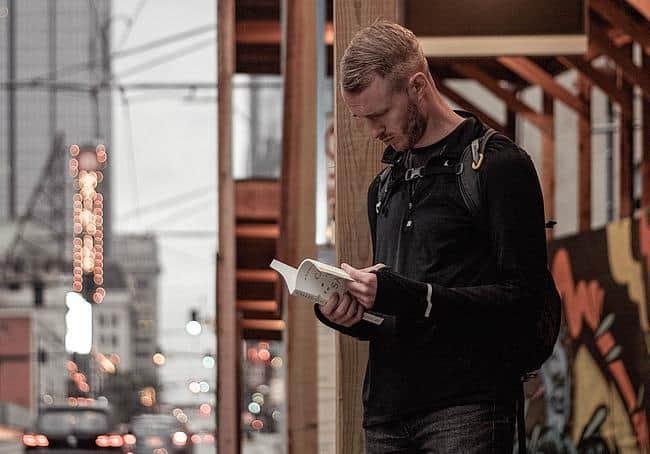Mann liest ein Buch auf der Straße
