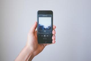 Hand hält Smartphone mit Spotify