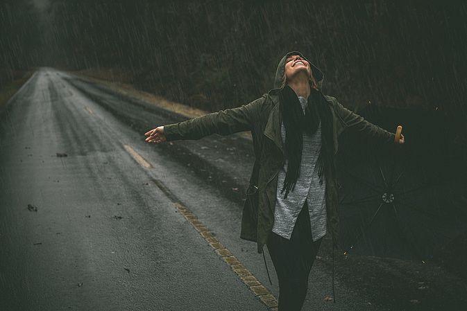 Frau steht im Regen