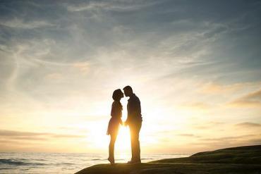 Ein Paar küsst sich während dem Sonnenuntergang