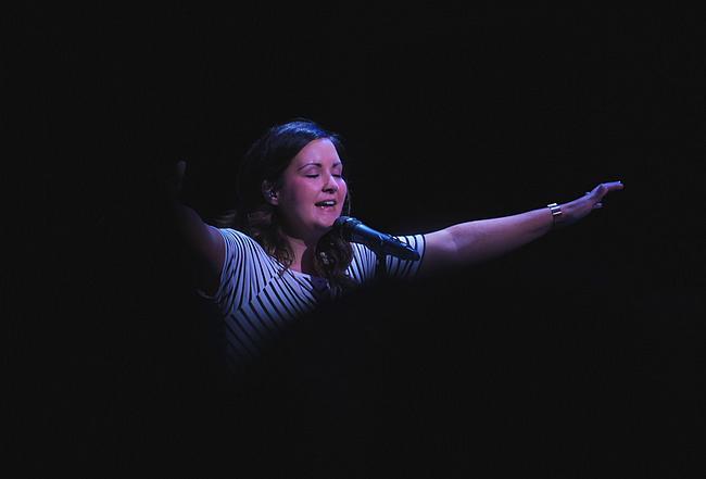 Frau singt. Der Hintergrund ist schwarz