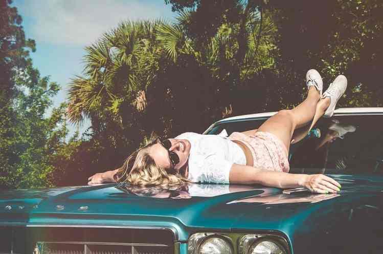Frau sonnt sich auf einem Auto