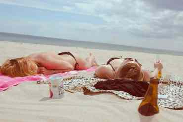 Zwei Frauen liegen am Strand