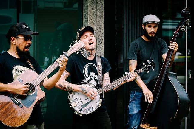 Drei Männer sind als Straßenmusiker tätig