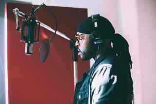 Mann singt mit Kopfhörer im Studio