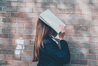 Frau hält ein Buch über ihren Kopf