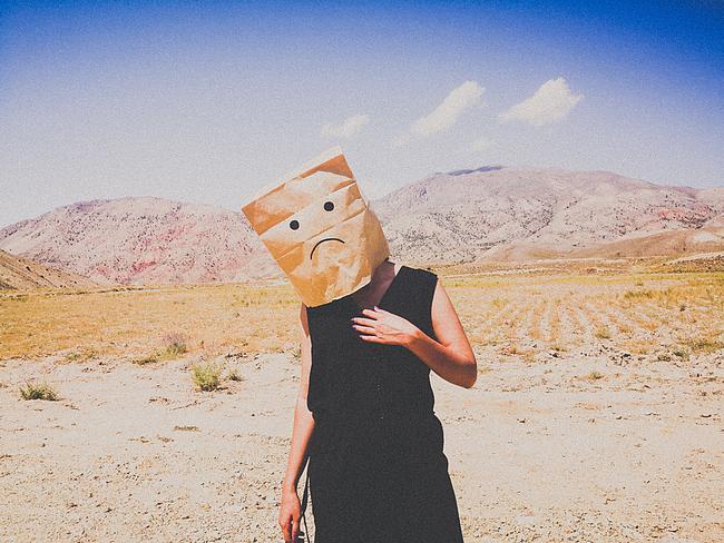 Frau mit trauriger Tüte über dem Kopf