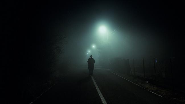 Mann steht auf einer nebligen Straße