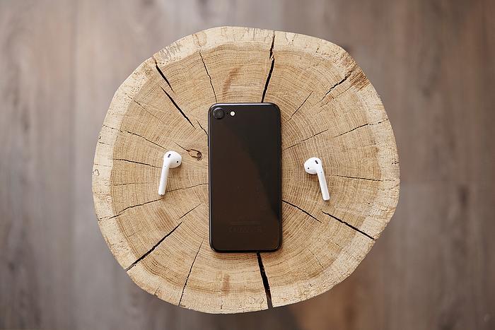 2 True Wireless In-Ear-Kopfhörer und ein Smartphone