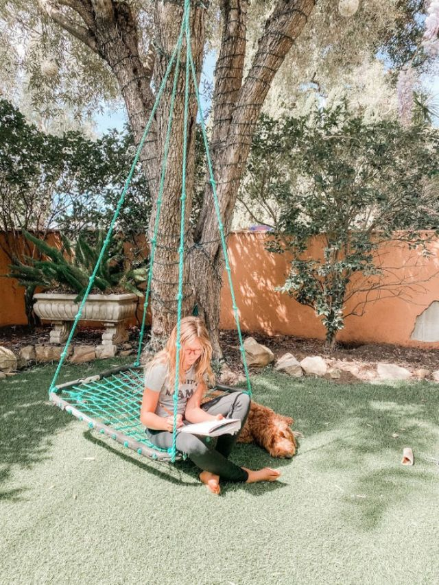 girl sitting on a swing doing homework with dog beside her | covid 19 homeschool schedule | Poplolly co
