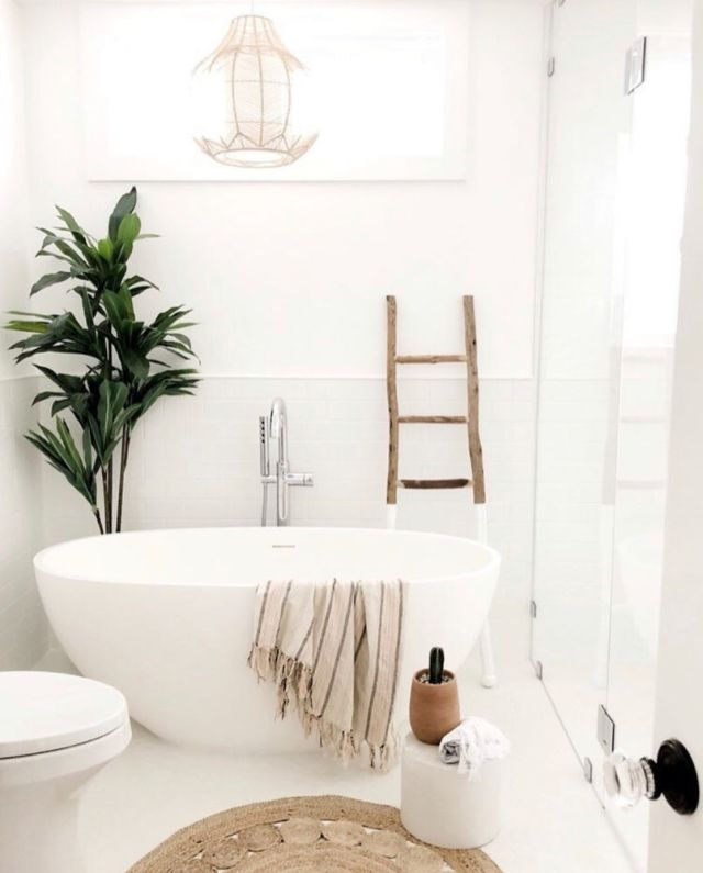bright white natural coastal bathroom with freestanding tub, jute rug, rattan light, ladder and plant | Poplolly co