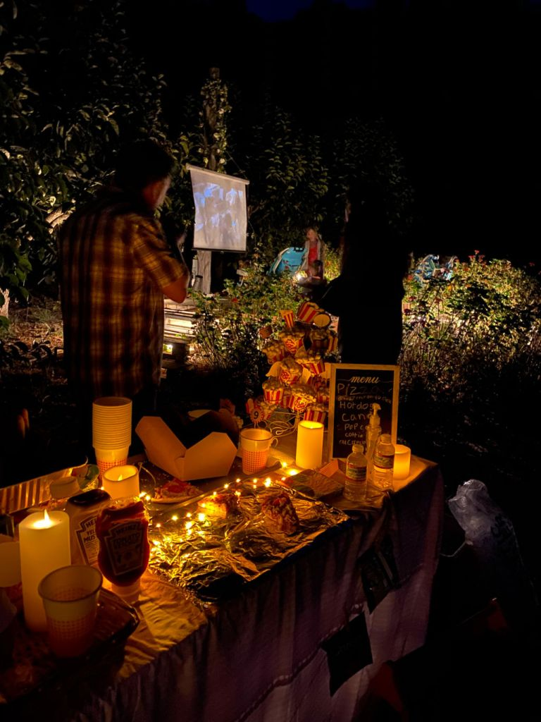 candles and twinkle lights illuminate a table of snacks for a backyard movie night | Poplolly co