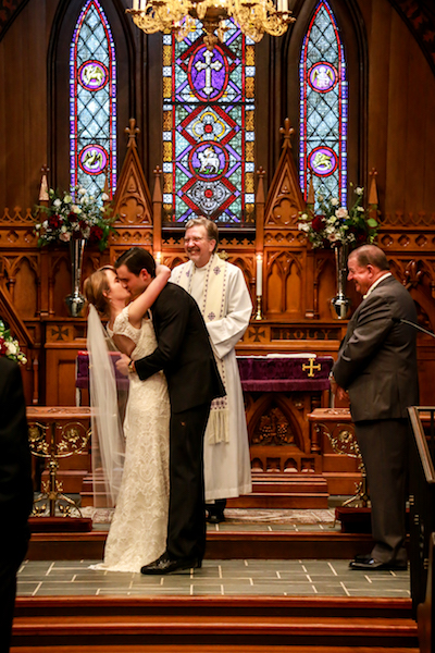 Bride and groom kissing in ceremony
