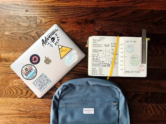 A laptop, a notebook, and a backpack lie on the floor