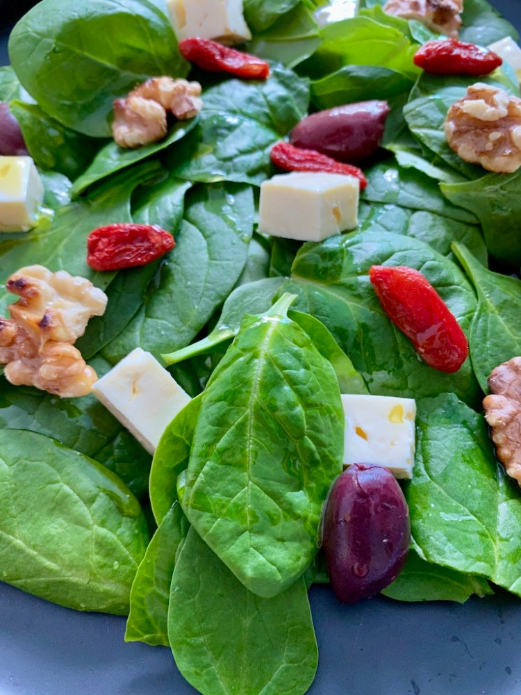 Healthy baby spinach leaves salad with feta cheese, goji berries, walnuts and kalamata olives