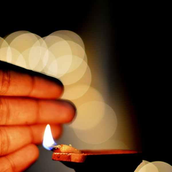 hand close to a lit diya
