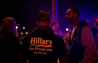 "Right across from the entrance of Washington University, Trump supporters have set up a display titled ""Hillary's House of Horrors"". Two police vehicles are parked right next to it, with the officers out of the vehicles. An African American couple talks to two supporters about their political leanings."