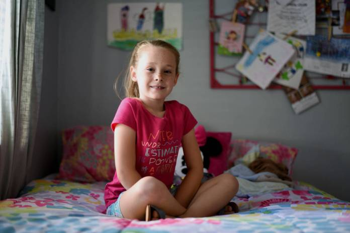 Gracie (7) poses for a picture in her room in Pleasant Hill, Calif., surrounded by princess and Minnie Mouse imagery. (Lauren Hanussak/KQED)