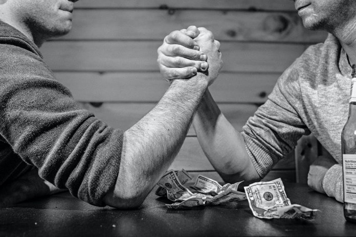 Two men betting over an arm wrestle