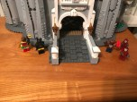 Batman and Robin fight villains at the gate of the castle