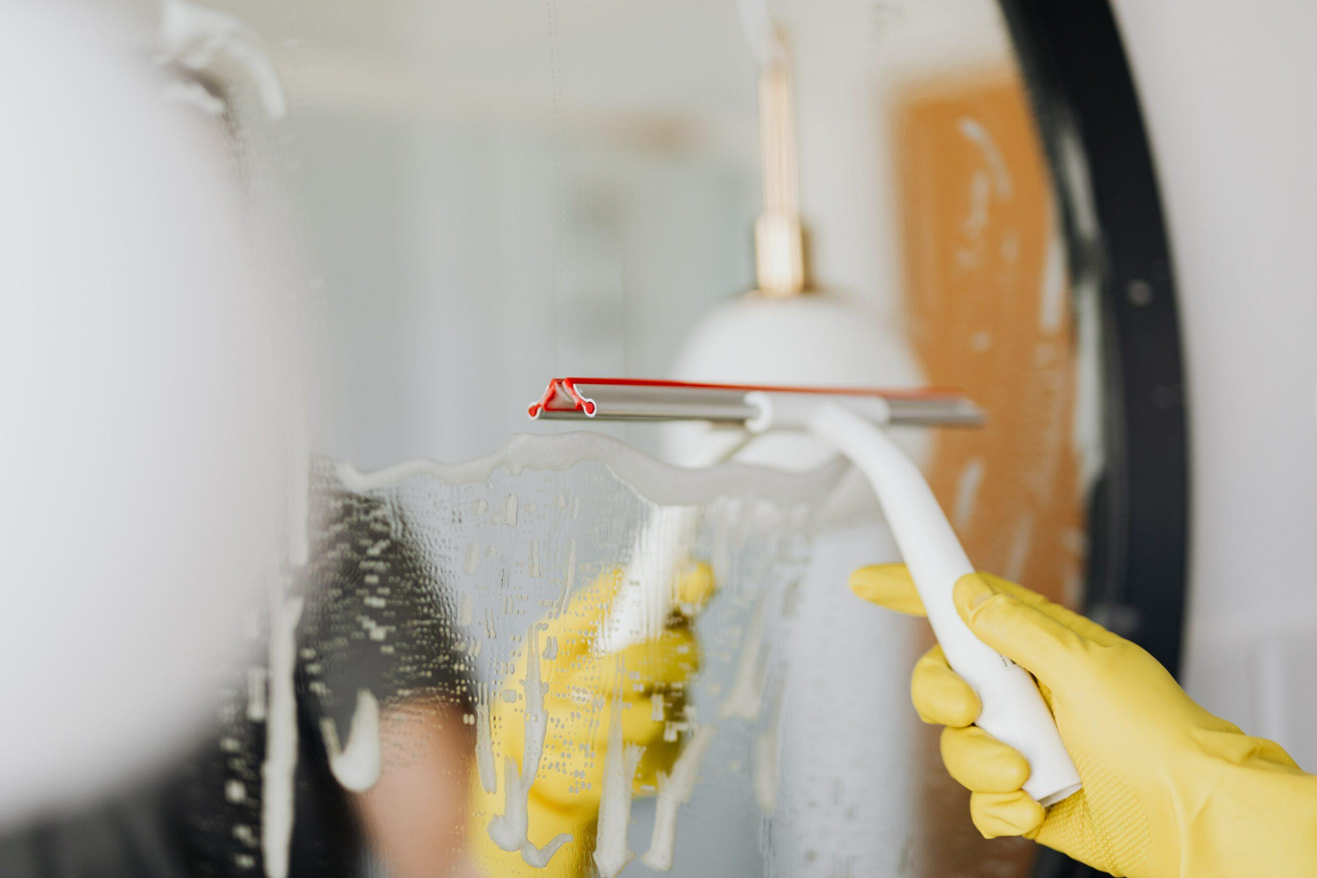 Profesjonalne czyszczenie lustra za pomocą ściągaczki do szyb