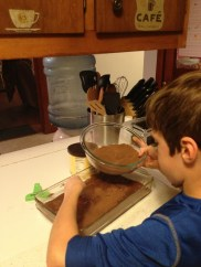 Noah is puttin the lava ingredients on the batter.