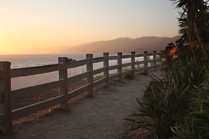 A view over Santa Monica beach from a walking trail, hills and sunset in the background.