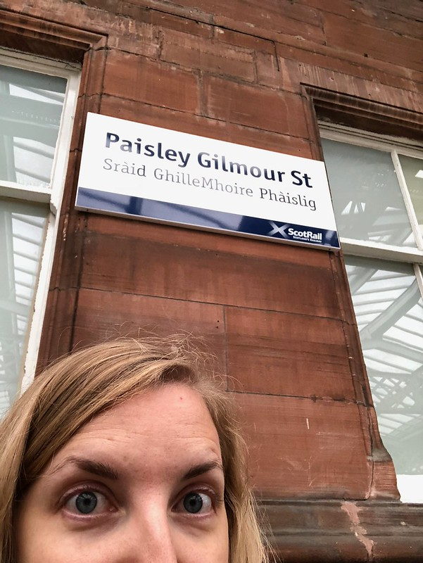 Tired selfie at the Paisley Gilmour Station, with signage translated into Gaelic