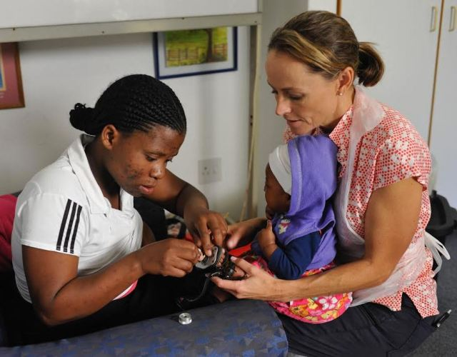 Steps Programme Manager for Training and Clinic Support assisting a mother with putting on a clubfoot brace at Maitland Cottage Clinic, supported by Steps Clubfoot Care.