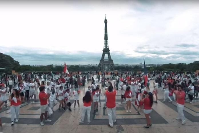 Cerca de un centenar de peruanos participaron en flashmob de marinera al pie de la Torre Eiffel, en homenaje al aniversario patrio. Foto: Captura TV