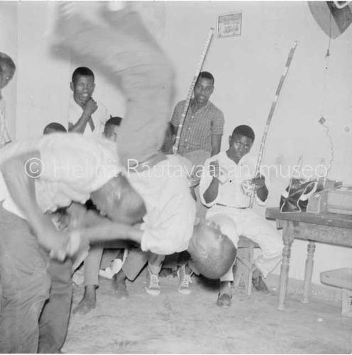 Mustavalkoisessa kuvassa vietetään todennäköisesti Boa Viagem -juhlaa. Kuvassa pelataan capoeiraa tuntemattomassa rakennuksessa. Etualalla on kaksi miestä peliasennoissa ja taustalla näkyy joukko miehiä, jotka säestävät peliä musiikilla. Pelaavista miehistä toinen heittää juuri voltin. Soittajilla erottuu ainakin kaksi berimbauta. Rakennuksen lattia on kuviollinen ja taustalla näkyy sivupöydällä jokin laite, mahdollisesti kelanauhuri.