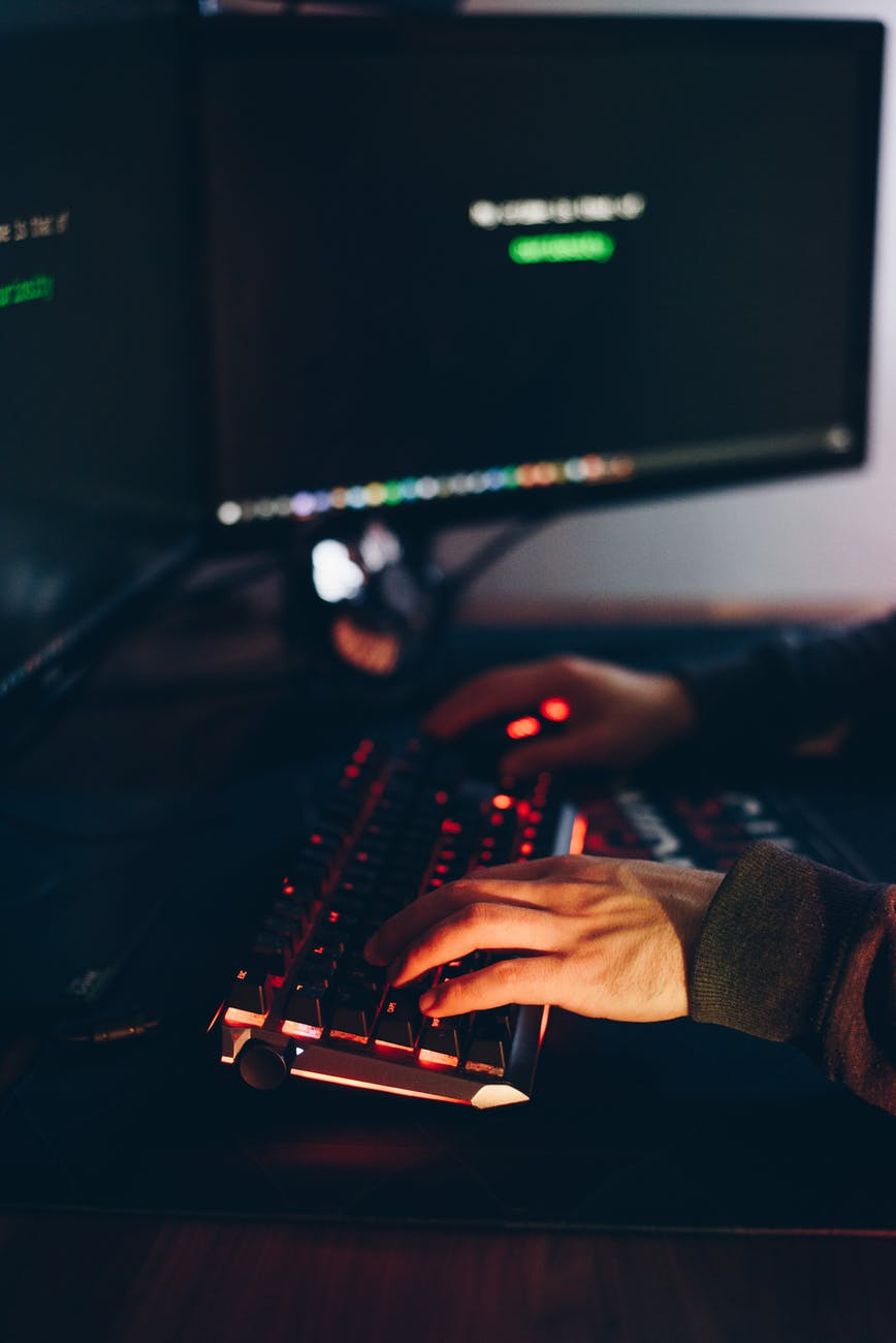 faceless hacker accessing secret information on computer in twilight