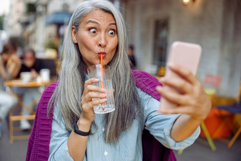 Funny mature Asian woman drinks water taking selfie with cellphone in cafe